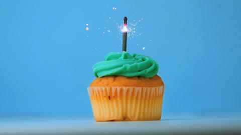 Sparkler burning on blue birthday cupcake Live Action