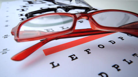 Close up of two pairs of glasses falling on eye test Footage