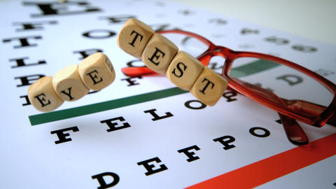 Eye test dice falling onto eye test with red reading glasses Live Action
