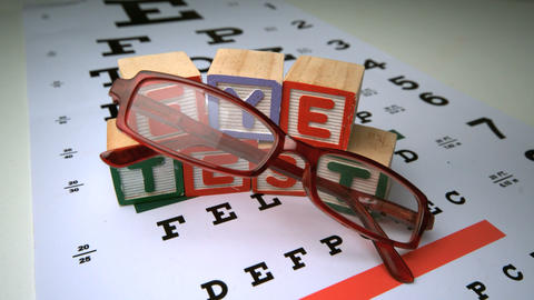 Glasses falling onto eye test with wooden blocks spelling out eye test Footage