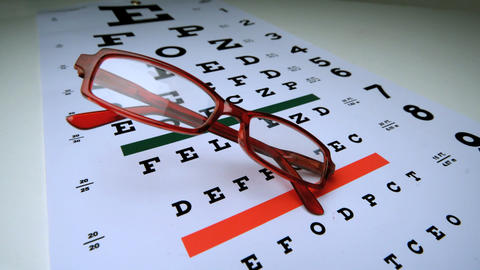 Red reading glasses falling onto an eye test Footage