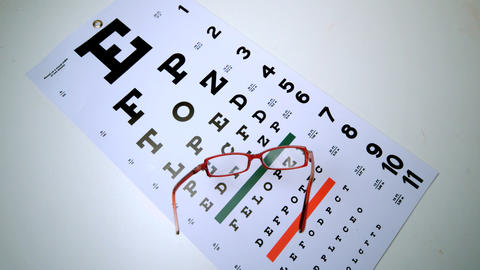 Red reading glasses falling onto eye test overhead Stock Video Footage