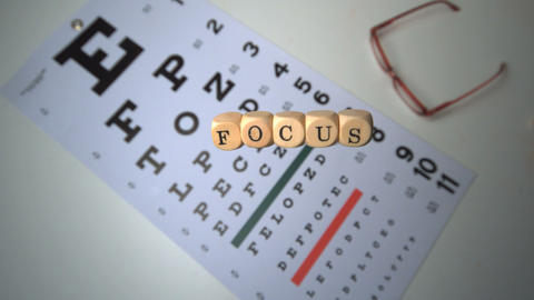 Dice spelling out focus falling onto eye test besi Stock Video Footage