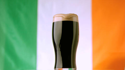 Head of pint of stout spilling over Stock Video Footage
