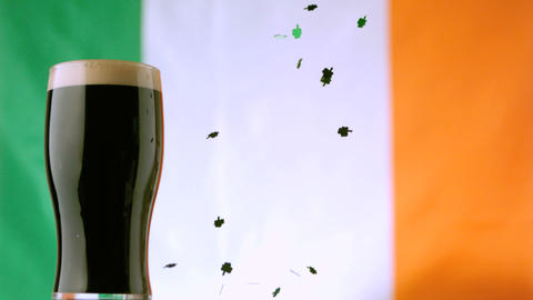 Shamrock confetti falling beside pint of stout Footage