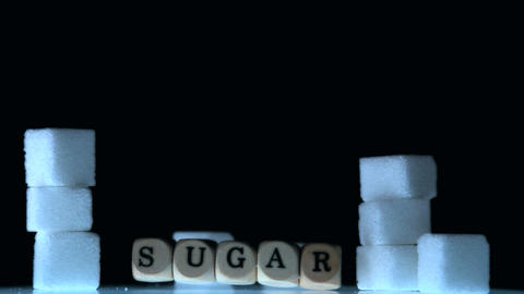Dice spelling out sugar falling beside sugar cubes Live Action
