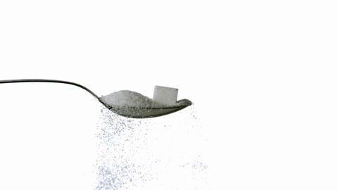 Sugar spilling off spoon with sugar and sugar cube Stock Video Footage