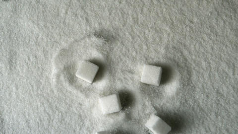 Many sugar cubes falling into pile of sugar Live Action