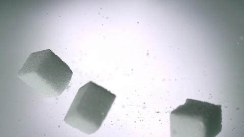 Sugar cubes falling onto white surface Stock Video Footage