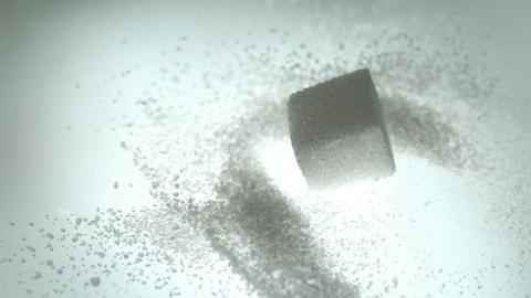 Sugar cube falling onto pile of powdered sugar Live Action