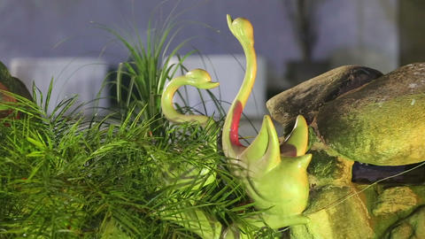 decorative green swans are near the rocks Footage