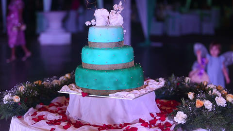 wedding cake stands on a table surrounded by fresh Footage