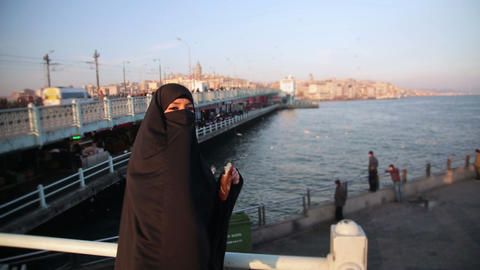 Woman dressed with black headscarf, chador eating, Footage