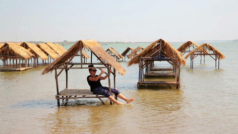 tourist girl enjoying bungalows inside river Footage