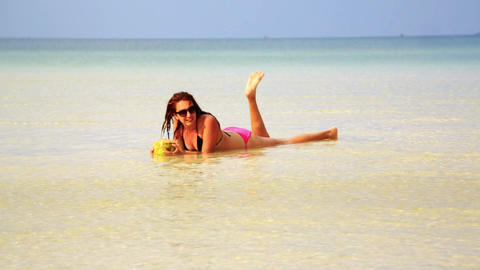 Woman sunbathing crystal water drinking coconut en Stock Video Footage