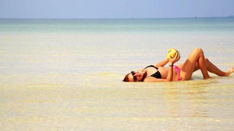 Woman sunbathing crystal water drinking coconut en Footage