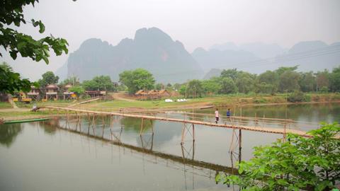 people passing bamboo bridge on limestone mountain Footage