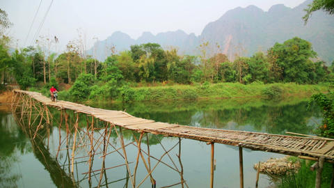 Passing bamboo bridge by motorbike, limestone view Footage