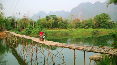 Passing bamboo bridge by motorbike, limestone view Stock Video Footage