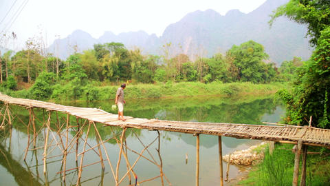 VANG VIENG, LAOS - APRIL 2014: crossing river on b Stock Video Footage