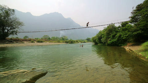 Tourist woman crossing dangerous bamboo suspension Footage