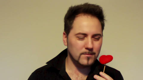 Guy kissing a heart on the stick 2 Stock Video Footage