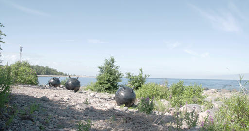 Three Big Sea Mines Found On The Rocky Shore Of Th stock footage