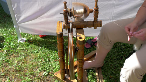A man is pedalling the spinning wheel to create a  Footage
