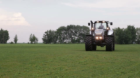 Gray Tractor Rides On The Green Field stock footage