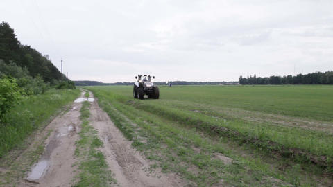 gray tractor rides on the green field Footage