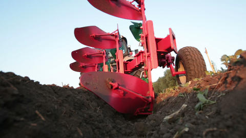 Tractor plowing the black earth plow field at suns Stock Video Footage