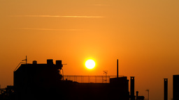 Sun Sets Behind Silhouetted Building In The City stock footage