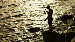 Silhouette Of A Man Fishing At Sunset 1 stock footage