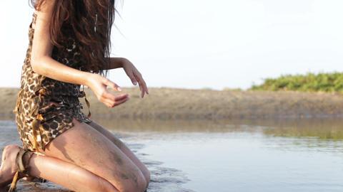 primitive woman kneeling near the water Stock Video Footage