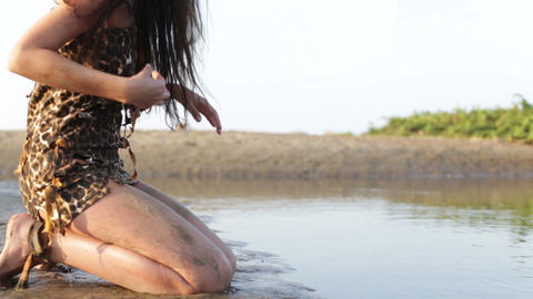primitive woman kneeling near the water Footage