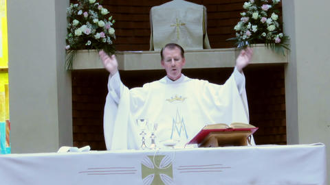 Catholic priest reads prayer from the Bible during Footage