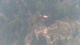HD2009-8-1-18 Terr mtn forest fire helo and bucket follow Stock Video Footage