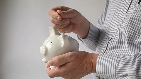 businessman puts pennies in piggy bank Footage