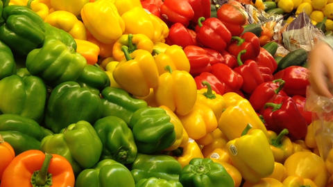 Woman selecting yellow peppers in grocery store Footage