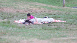 Mother and daughter lying down on the grass Footage