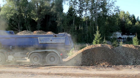 A dump truck unloading sand and gravel and house Footage