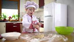 Little Cook Puts Some Flour On Dough Before Rollin stock footage
