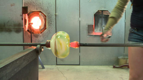 Glass blower attaching base on vase Live Action