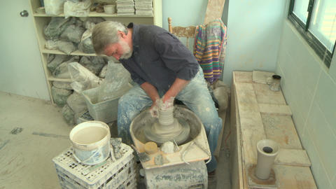 Wide shot potter shaping a tall vase 1 Footage