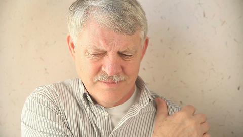 man rubs sore shoulder Footage