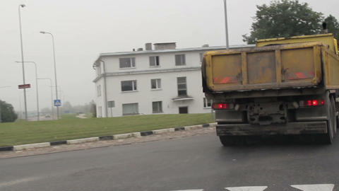 Yellow dump truck driving transporting materials a Footage