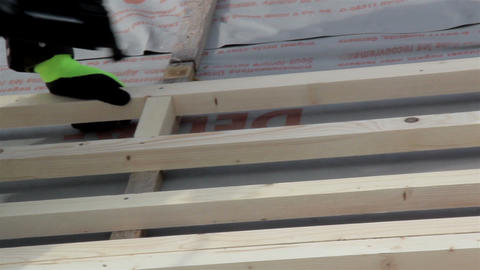 Roofer Working On Nailing The Wood Lath Using A Na stock footage