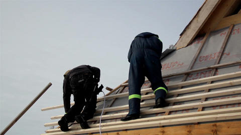 Two roofers fixing wooden lath roof with their equ Footage