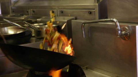 Chef tossing vegetables in a wok over a large flame ビデオ