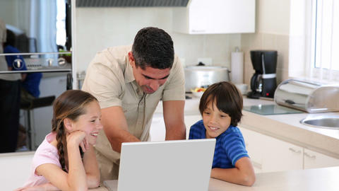 Father using the laptop with his children Footage